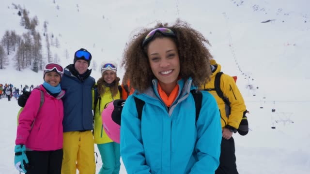 african american young woman at the alps facing camera smiling and group of friends standing behind her - stazione sciistica video stock e b–roll