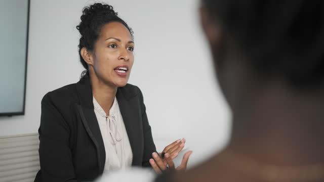 vídeos y material grabado en eventos de stock de mujeres de negocios africanas e hispanas conversando durante la reunión - foto natural