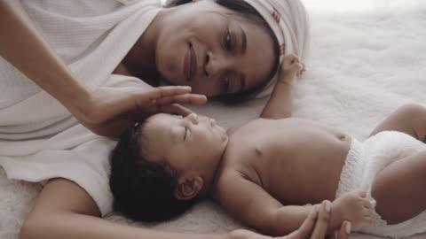 afrikansk pojke (2-5 månader) liggande på sängen med sin mamma - afroamerikanskt ursprung bildbanksvideor och videomaterial från bakom kulisserna