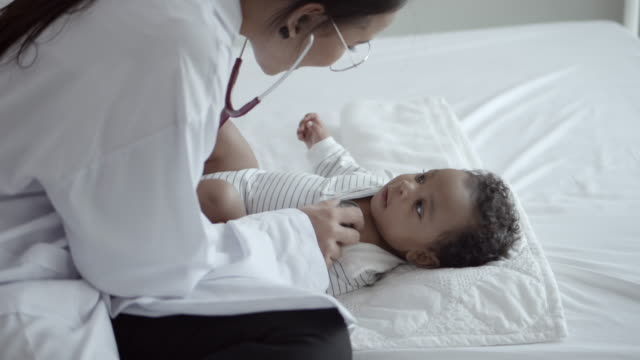 vídeos de stock e filmes b-roll de african baby checkup with stethoscope,slow motion - estetoscópio