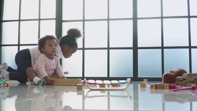 african baby girl sitting with innocence, play wooden math toy with innocence feeling with a little sister in the living room, concept of preschool, childhood, playing of a sibling, low angle view. - 2 3 years stock videos & royalty-free footage