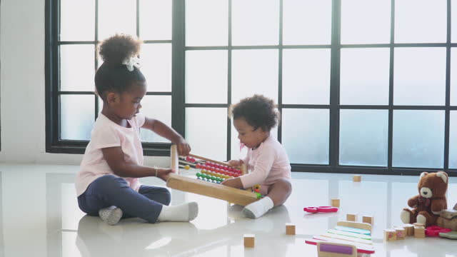 african big sister snatch wooden toy form a baby girl sitting with innocence in the living room, concept of preschool, childhood, playing of a sibling, low angle view. - 2 3 years stock videos & royalty-free footage