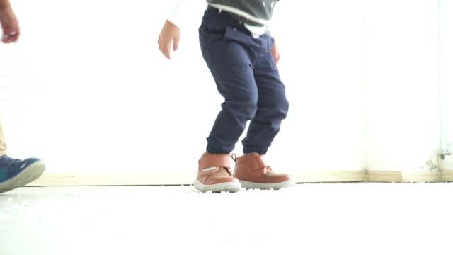 vídeos de stock, filmes e b-roll de menino africano e sapato de amigo vestindo peça de pano de inverno e saltar sobre a neve artificial - low angle view