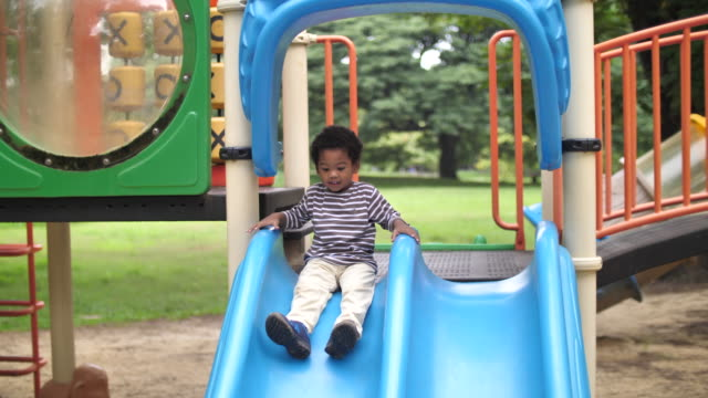 vídeos y material grabado en eventos de stock de african boy en playground deslizándose hacia abajo - tobogan