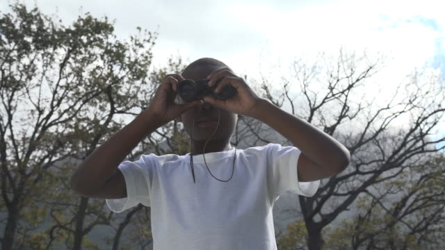 la ms african boy looking through binoculars in garden/ cape town/ south africa - discovery stock videos & royalty-free footage