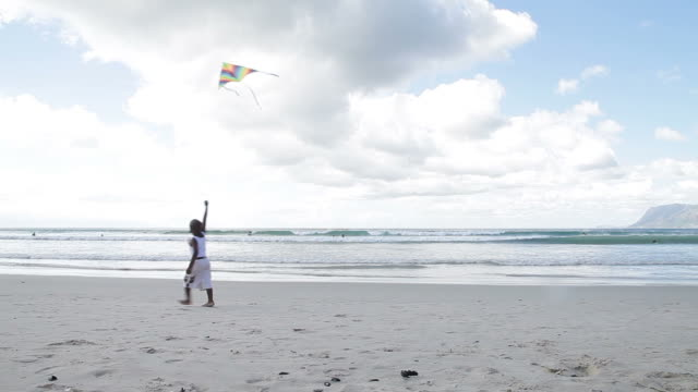 African boy walking on the beach with his kite