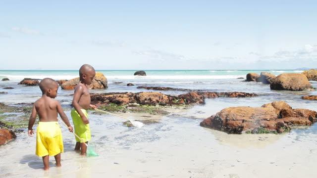 african boys fishing with nets on the beach - badbyxor bildbanksvideor och videomaterial från bakom kulisserna