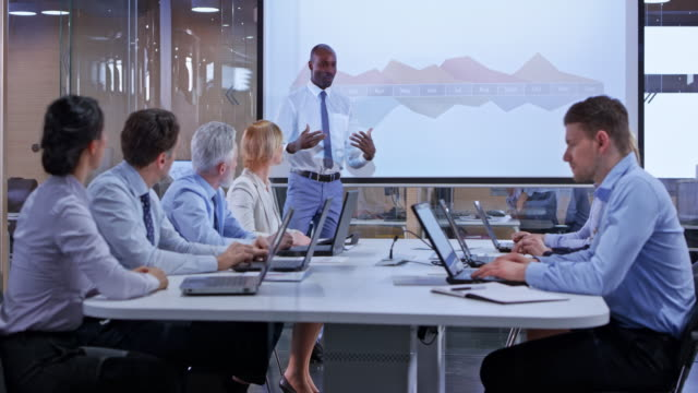 ds african business man giving a presentation in a glass conference room - sala conferenze video stock e b–roll
