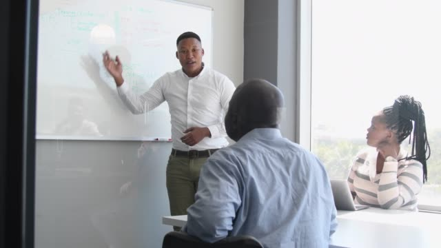 african businessman making presentation to business colleagues - whiteboard stock videos & royalty-free footage