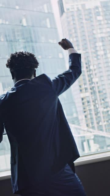 vídeos de stock, filmes e b-roll de empresário africano no cargo com gesto vencedor. admirando o panorama da cidade. vídeo vertical - vestuário de trabalho formal