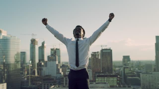 勝利のジェスチャーで屋根の上に立っているアフリカのビジネスマン - ロールモデル点の映像素材/bロール