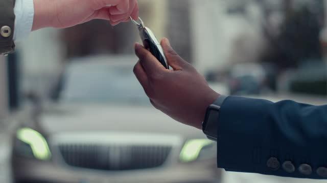 新しい車に鍵を取るアフリカのビジネスマン。手でクローズアップ - 車のキー点の映像素材/bロール