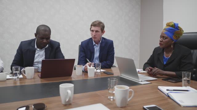 vídeos y material grabado en eventos de stock de empresaria africana presiendo una reunión de negocios en su oficina - presidente de organización
