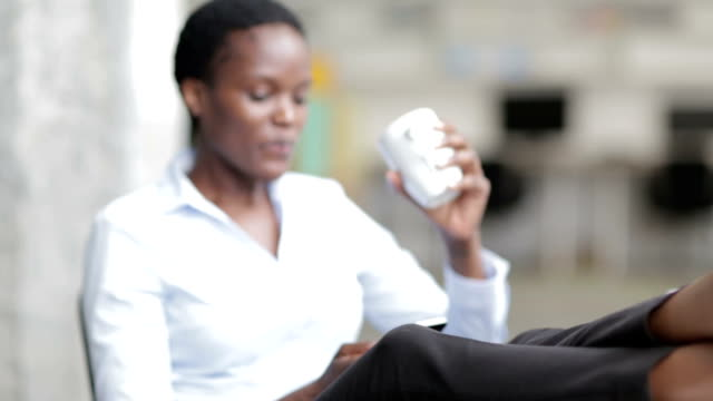 HD: African Businesswoman having Coffee Break in office texting.