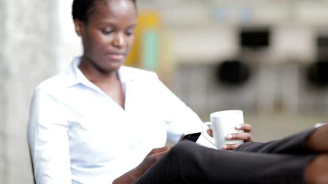 HD: African Businesswoman having Coffee Break in office texting.