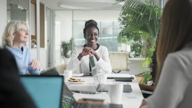 vidéos et rushes de femme d'affaires africaine s'asseyant à la tête de la table de salle de conseil - table de salle de réunion