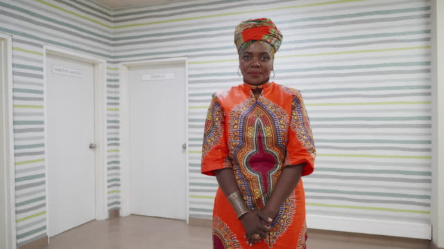 african businesswoman wearing traditional chitenge, smiling at the camera - zambia stock videos & royalty-free footage