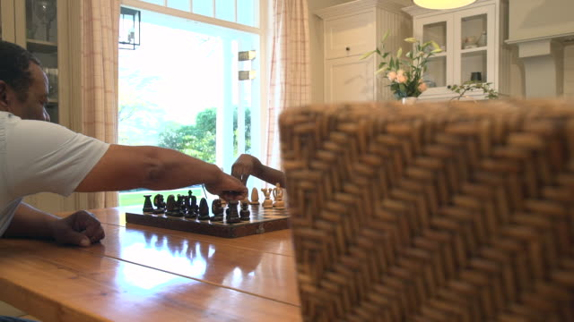 stockvideo's en b-roll-footage met ms of african child being taught to play chess by grandparent/ cape town/ south africa - spelletjesavond