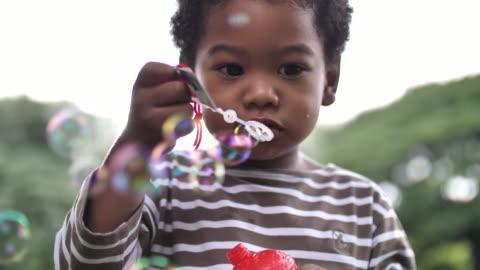 stockvideo's en b-roll-footage met afrikaans kind blazen bubbels bij camera - child