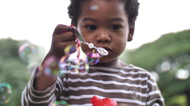 african child blowing bubbles at camera - messing about stock videos & royalty-free footage