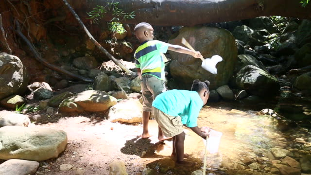 African children fishing with nets in a pond