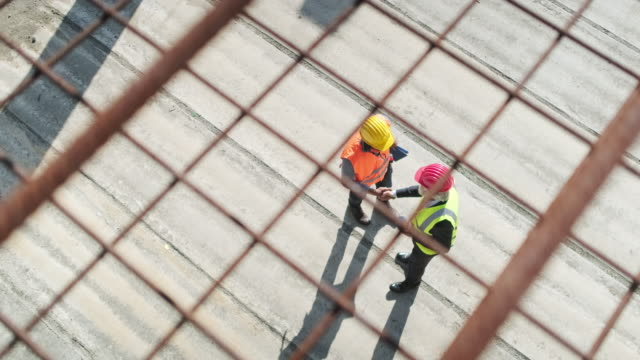 african construction site foreman greeting caucasian manager - construction industry stock videos & royalty-free footage