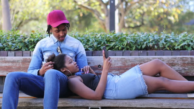 african couple relaxing at the park and using their mobile phones - teenage couple stock videos & royalty-free footage
