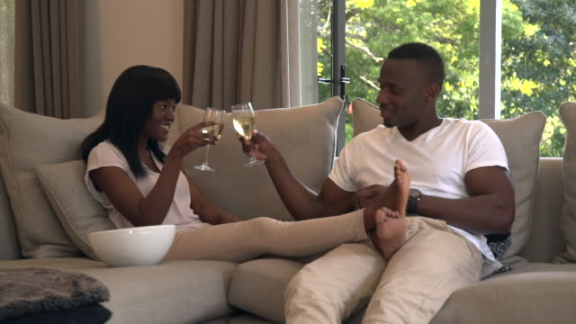 vídeos y material grabado en eventos de stock de ls african couple relaxing on sofa and drinking wine/ cape town/ south africa - color crema