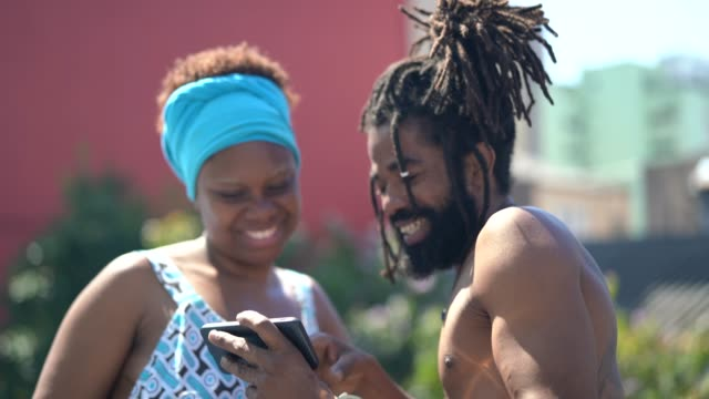 vídeos de stock, filmes e b-roll de casal africano usando o celular em dia de verão - adereço de cabeça