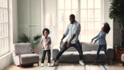 African dad dancing having fun with kids in living room