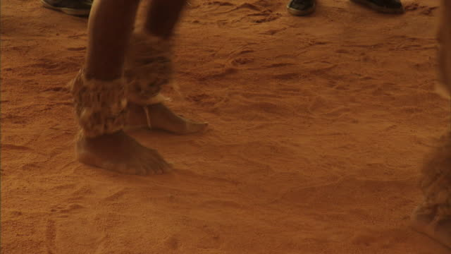 African dancers' feet stomp around as they dance in red dirt.