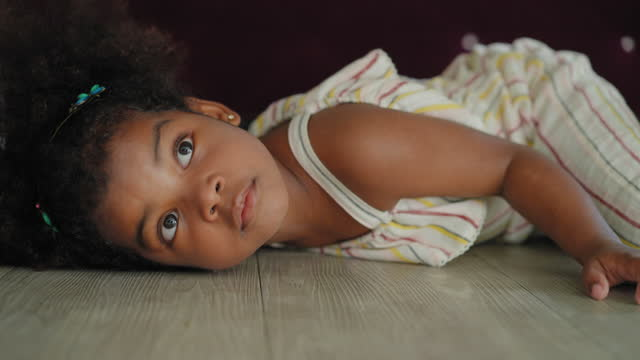 african daughter laying down on the floor, hiding under a table after playing hard in the living room with feeling happy, smiling, laughing. concept of preschool. - hiding stock videos & royalty-free footage