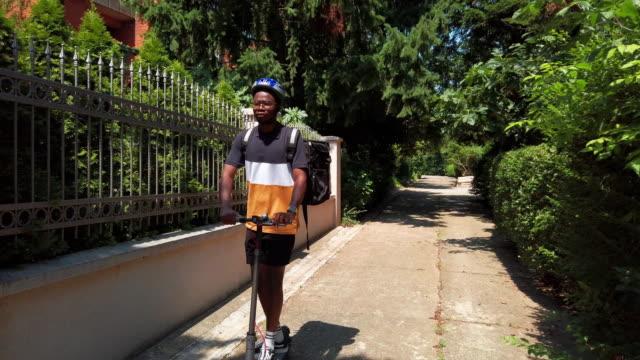 african deliver person reiten elektroroller und liefern lebensmittel - electrical equipment stock-videos und b-roll-filmmaterial