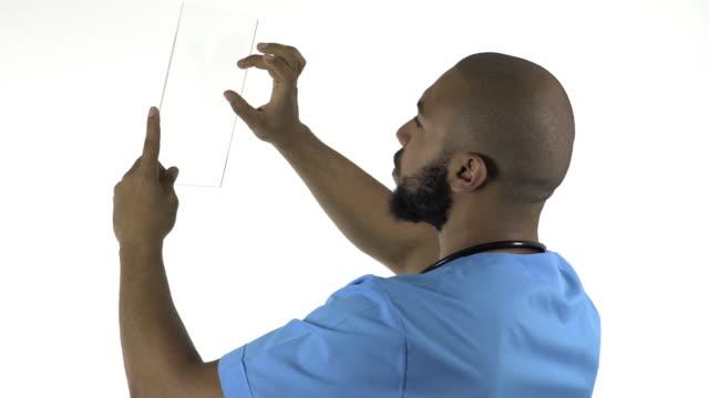 Médico descendencia africana usando tableta digital sobre fondo blanco