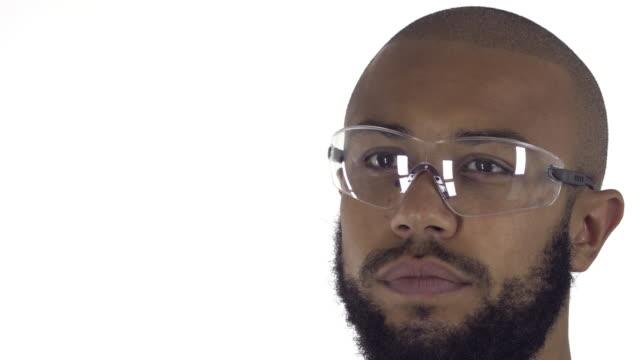 afrikanischer herkunft labor arbeiter auf weißem hintergrund - schutzbrille freisteller stock-videos und b-roll-filmmaterial