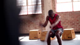 African descent man doing battle rope exercise in gym training