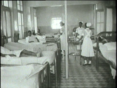 African doctors and nurses work in a maternity ward as a woman gives birth