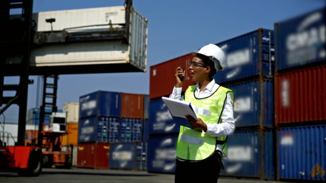 4k african engineer woman using a radio and clipboard working with cargo containers while standing on a commercial shipping dock - crane stock videos & royalty-free footage