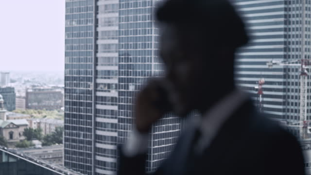 african ethnicity businessman making a call. city panorama - alla moda video stock e b–roll
