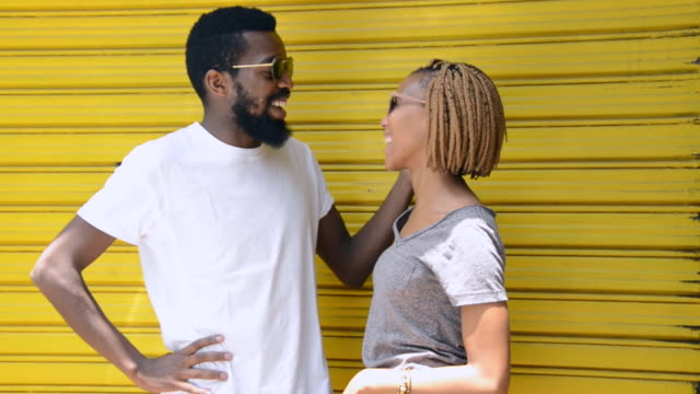 ms of african ethnicity couple talking in front of yellow background / johannesburg, gauteng, south africa - gelb stock-videos und b-roll-filmmaterial