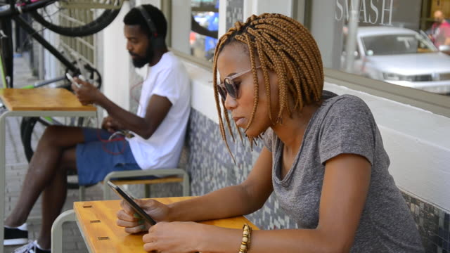 MS of African Ethnicity couple using portable devices in Braamfontein / Johannesburg, Gauteng, South Africa