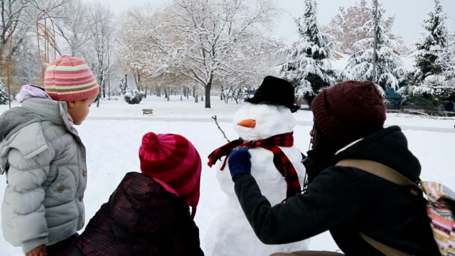 african ethnicity family making a snowman on the park - making a snowman stock videos & royalty-free footage