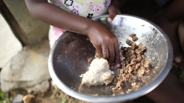 cu slo mo african ethnicity girl eating food with her hands in rural township/ vredefort/ south africa - armut stock-videos und b-roll-filmmaterial