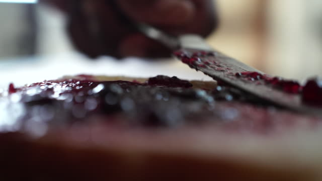 ecu slo mo african ethnicity hand spreading berry jam onto a slice of bread and butter/ johannesburg/ south africa - jam stock videos & royalty-free footage