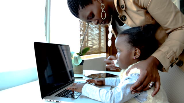 MS African ethnicity mother wiping her daughter's nose as child uses laptop computer, Johannesburg, South Africa
