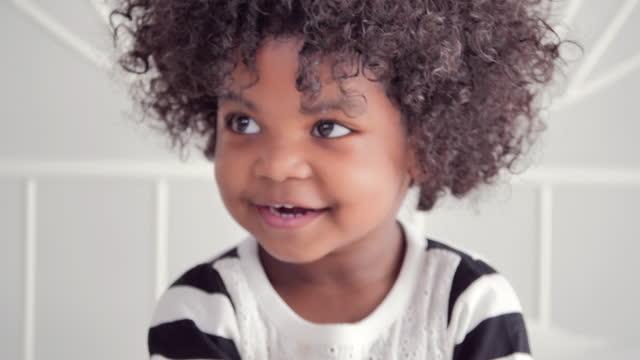 vídeos de stock, filmes e b-roll de a etnia africana de crianças de 2 a 3 anos fica em casa para prevenir epidemias de coronavirus ou covid-19.conceito de momentos familiares. - cabelo encaracolado