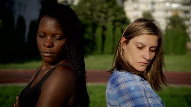 アフリカの民族女性と白人民族の女性は紛争を抱えている - 固定観念点の映像素材/bロール