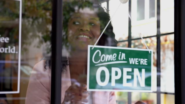 african ethnicity woman opening the store - english language stock videos & royalty-free footage