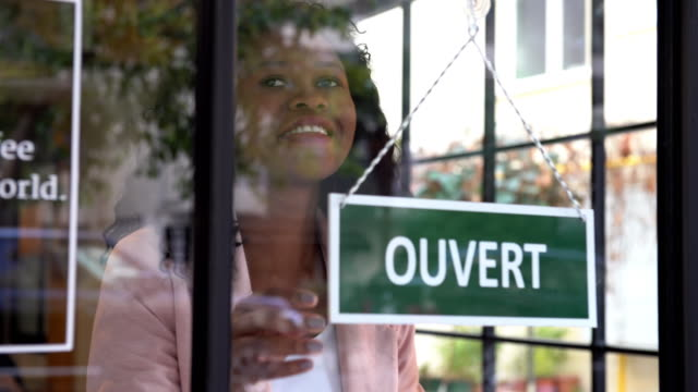 african ethnicity woman opening the store - french language stock videos & royalty-free footage