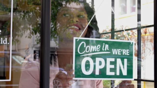 stockvideo's en b-roll-footage met afrikaanse etniciteit vrouw het openen van de winkel - bord open